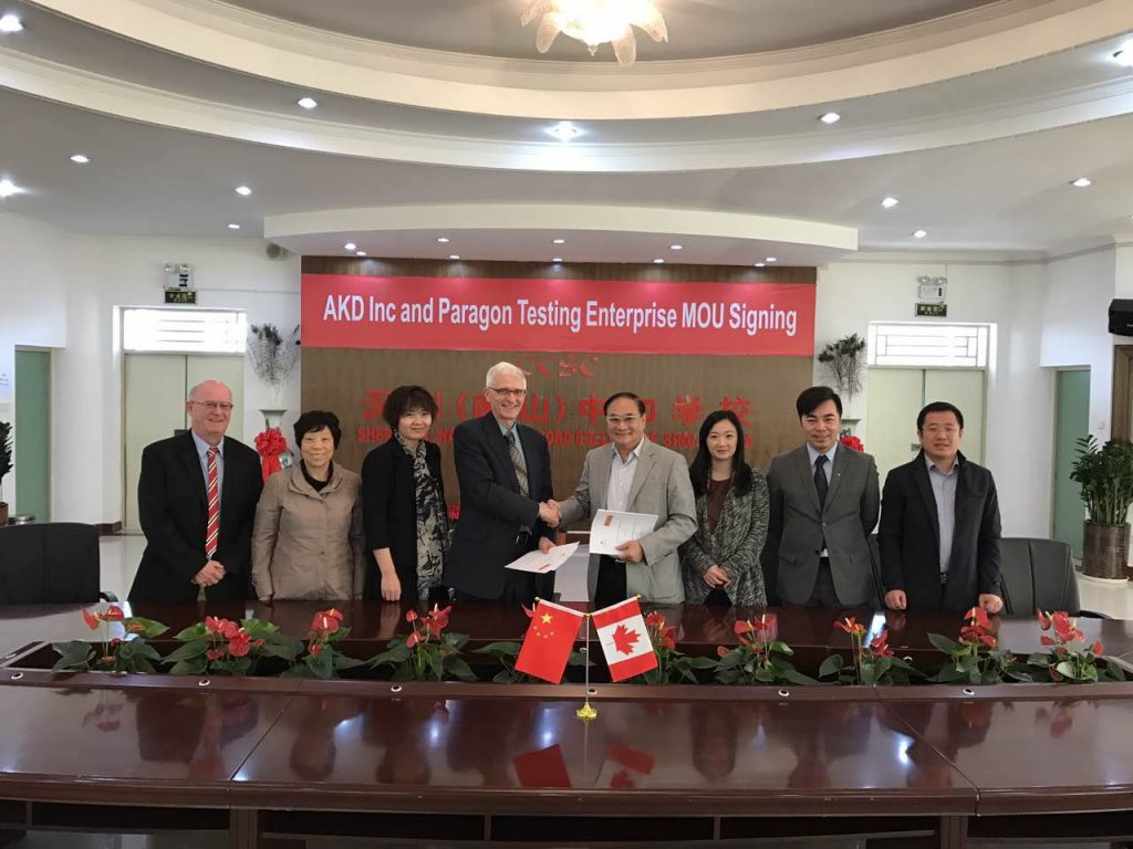 Dr. Donald Wehrung, CEO of Paragon Testing Enterprises, and Dr. Francis Pang, chairman of AKD Inc., shaking hands at the signing ceremony in Shenzhen, China.